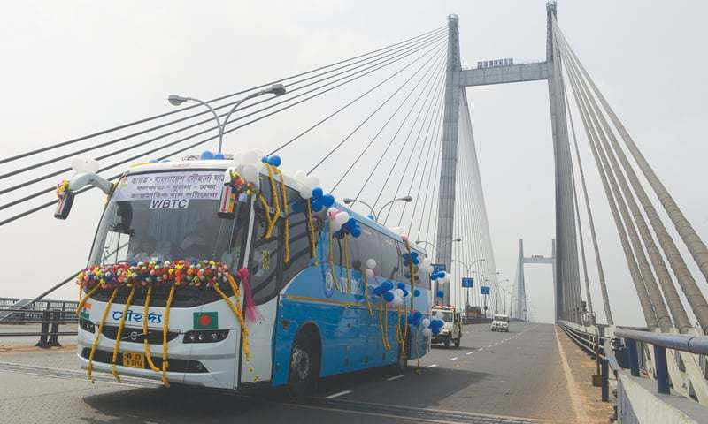 The newly launched Kolkata-Khulna-Dhaka bus drives over the Vibyasagar Setu (bridge) on the River Ganges after it was flagged off in Kolkata on Saturday. Bangladeshi Prime Minister Sheikh Hasina, her Indian counterpart Narendra Modi and West Bengal Chief Minister Mamata Banerjee inaugurated the bus service remotely from New Delhi.—AFP