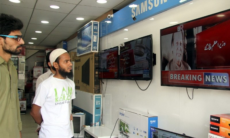 KARACHI: People watch TV coverage of the Supreme Court's verdict on the Panama Papers case in Saddar on Thursday.—PPI