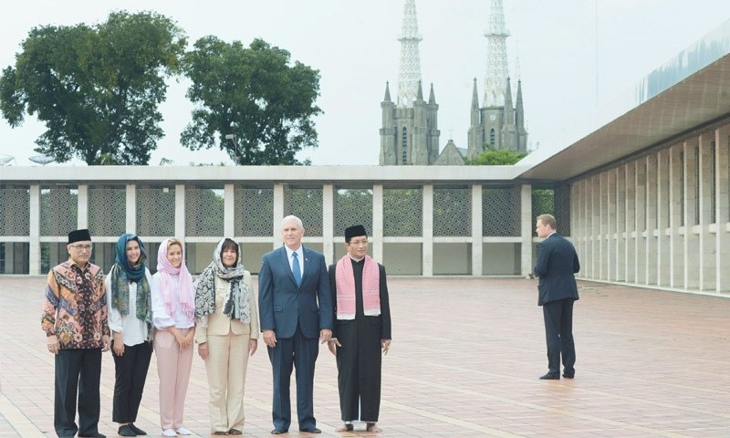 JAKARTA: US Vice President Mike Pence (fifth from left) poses for a photo with, from left to right, Chairman of Istiqlal Mosque Muhammad Muzammil Basyuni, his daughters Audrey and Charlotte, his wife Karen and the Grand Imam of the mosque Nasaruddin Umar, as the city's cathedral is seen in the background, during his visit to the largest mosque in South-east Asia on Thursday.—AP