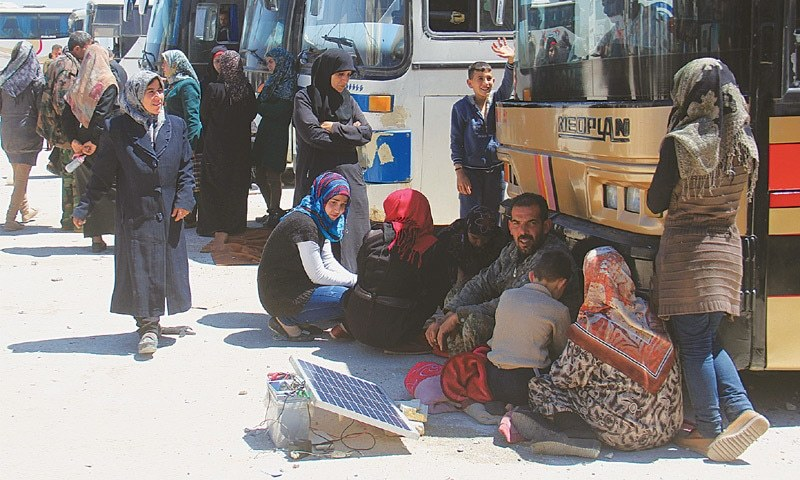 from the government-held towns of Fuaa and Kafraya that have been under a crippling siege for more than two years, Syrians sit in the shade of buses at the rebel-held transit point of Rashidin outside the government-held second city of Aleppo on Thursday as they wait for the resumption of the evacuation.—AFP