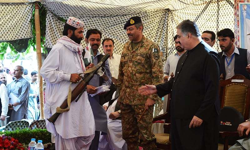 Suspected militants handing over their weapons to the chief minister. -Asmatullah Kakar