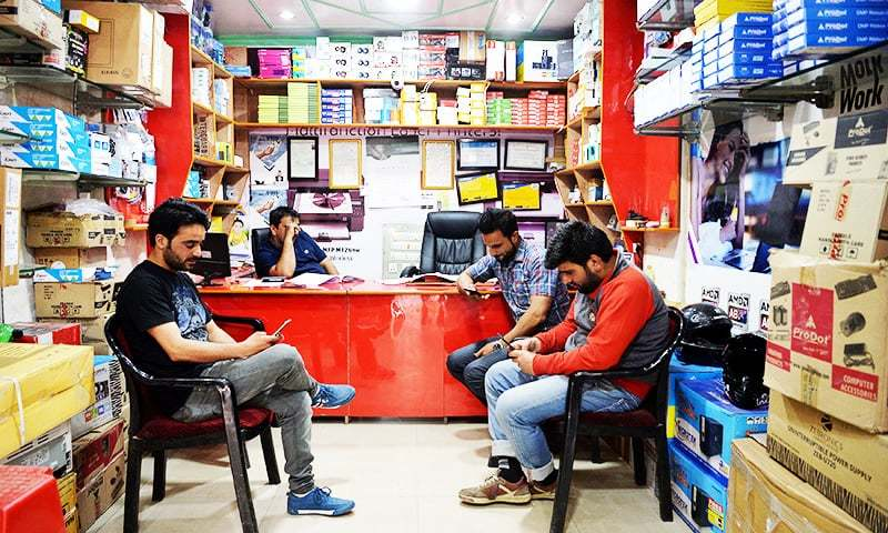 This photo shows Kashmiri men looking at their mobile phones in a shop in Srinagar.—AFP