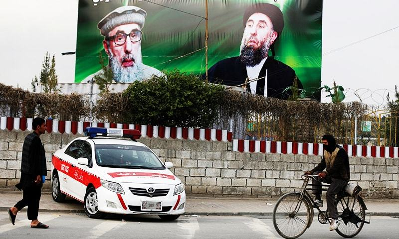 An Afghan man rides on his bicycle past a banner with pictures of Afghan warlord Gulbuddin Hekmatyar in Kabul, Afghanistan.—Reuters