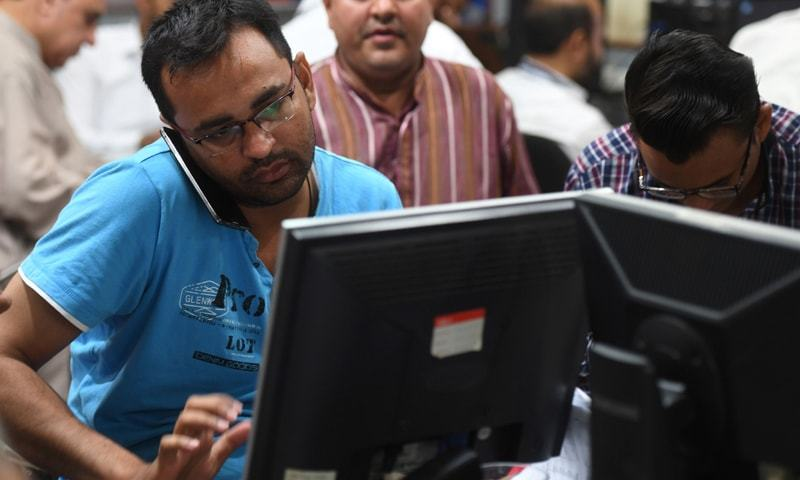 KARACHI: A stockbroker talks on the phone on Monday at the Pakistan Stock Exchange.—AFP