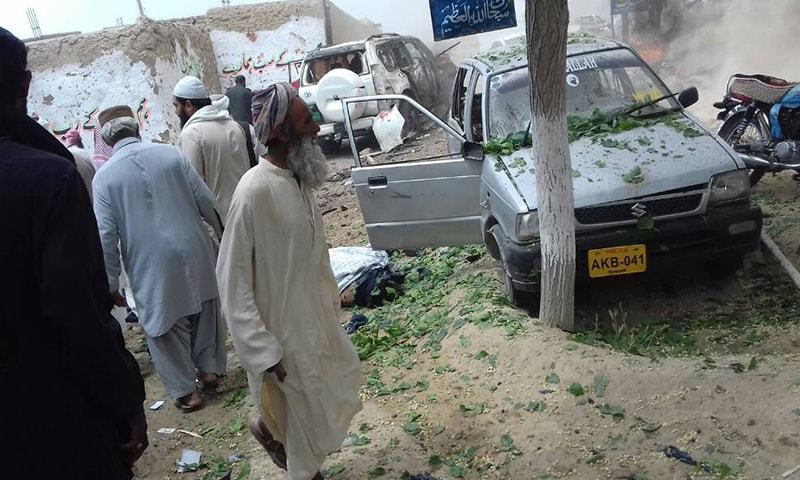 Men examine the site of the blast. — DawnNews