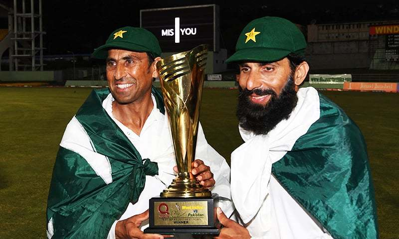 Younis Khan and captain Misbah ul Haq celebrate with the series trophy  after winning the final test match and the series 2-1 against the West Indies at the Windsor Park Stadium in Roseau, Dominica — AFP