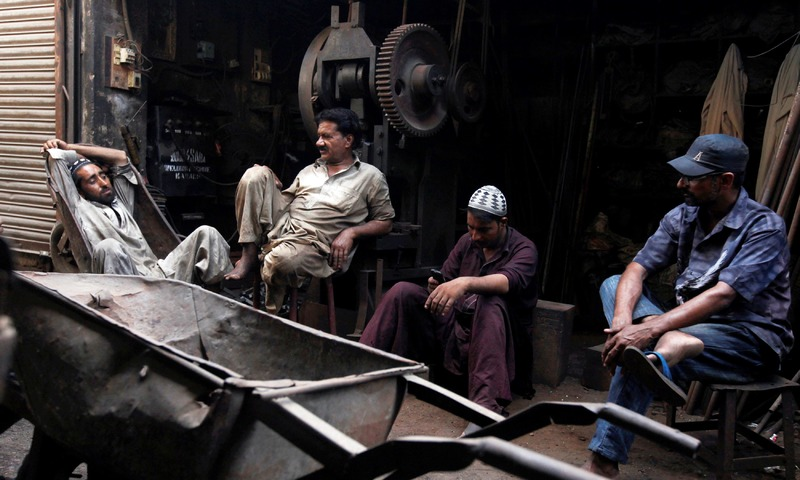 Workers sit outside a workshop during a power outage in Karachi. —Reuters