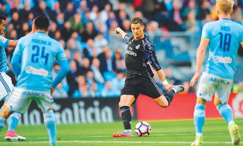 VIGO: Real Madrid's forward Cristiano Ronaldo shoots to score the opener during their La Liga match against Celta Vigo at the Balaidos stadium.—AFP