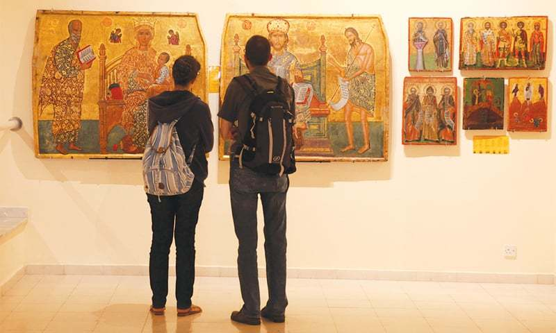 NICOSIA: Tourists look at icons in a museum in Cyprus on Friday. These were recovered by Cyprus after being stolen in the aftermath of Turkey's invasion in 1974.—Reuters