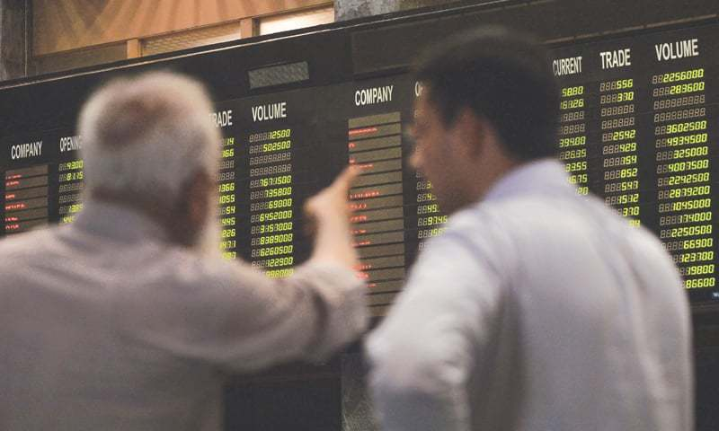Pakistani stockbrokers watch an index board showing the latest share prices during a trading session at the Pakistan Stock Exchange in Karachi on May 15.—AFP