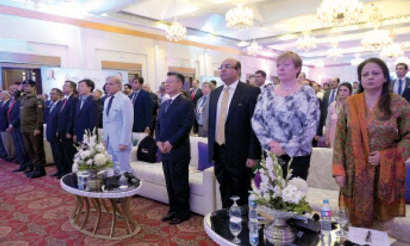 Chief Minister Shahbaz Sharif and participants in the international seminar on business opportunities stand in honour of the national anthem. — White Star