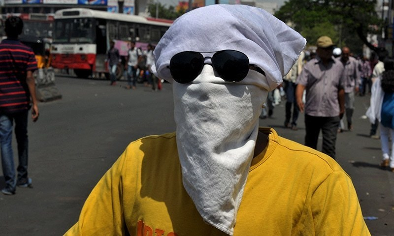An Indian man covers his face as drives on a scooter under the hot sun in Hyderabad on May 26, 2015. More than 430 people have died in two Indian states from a days-long heatwave that has seen temperatures nudging 50 degrees Celsius (122 degrees Fahrenheit), officials said May 25. Officials warned the toll was almost certain to rise, with figures still being collected in some parts of the hard-hit Telangana state in the south of the country, and with no end in sight to the searing conditions AFPHOTO/ Noah SEELAM