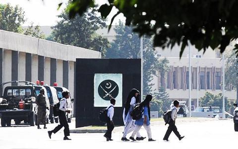 Children walk past the GHQ in Rawalpindi. — File