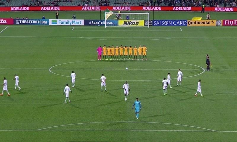 آسٹریلیا کے کھلاڑی میچ کے آغاز میں احتراماٍ کھڑے ہیں جبکہ سعودی عرب کے کھلاڑی فیلڈ میں پھیلے ہوئے ہیں— فوٹو: اے پی