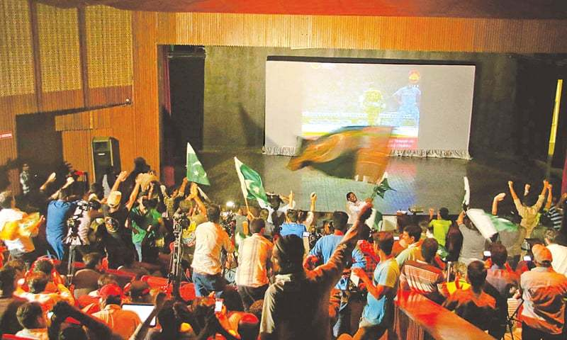 JUBILANT fans applaud as they watch the ICC Champions Trophy final between Pakistan and India on a big screen here on Sunday.—INP