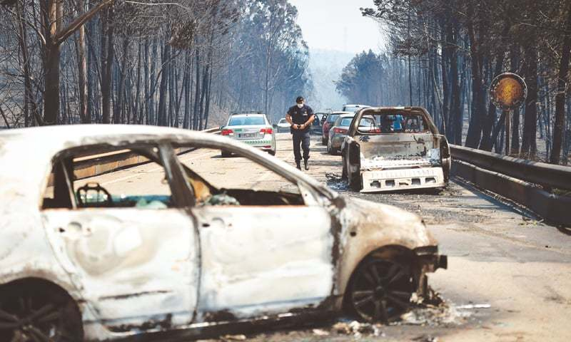Figueiro dos Vinhos (Portugal): A policeman walks on a road past burnt cars after the wildfire.—AFP