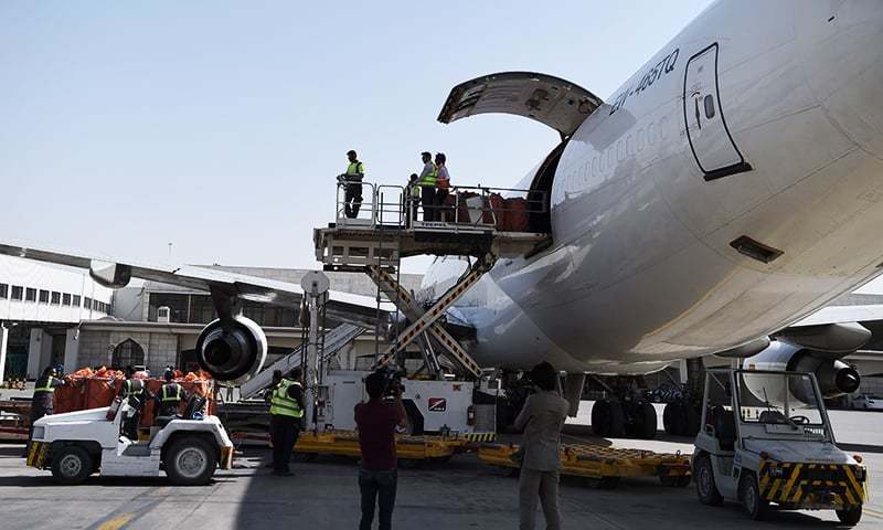 Afghan airport workers load the first cargo plane bound for India. ─ AFP