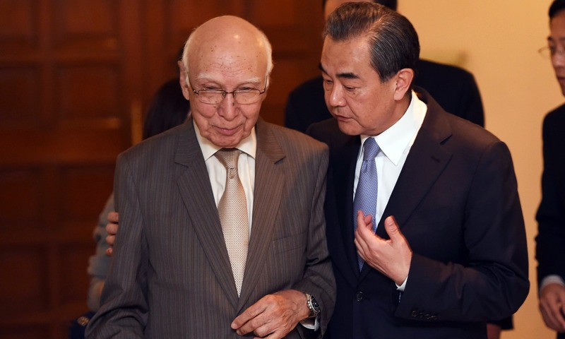 Chinese Foreign Minister Wang Yi  and Adviser to the Prime Minister on Foreign Affairs Sartaj Aziz arrive for a press briefing. —AFP