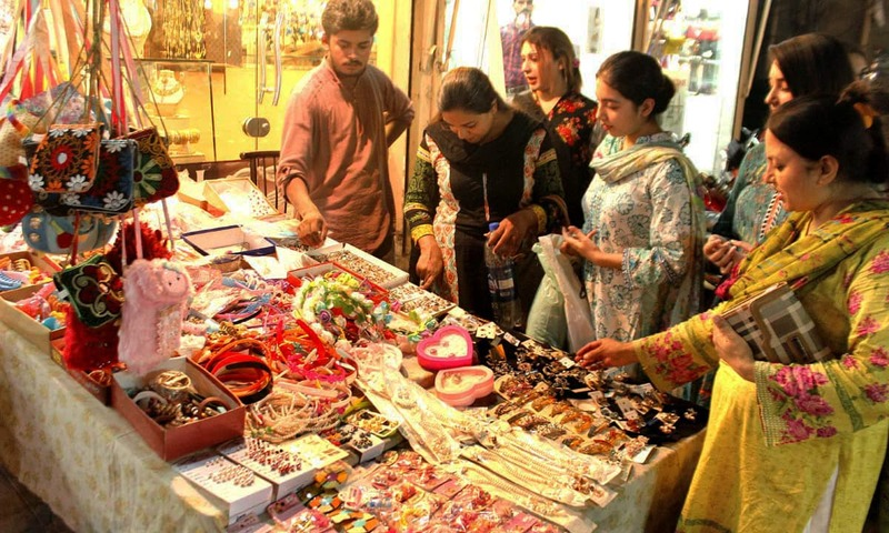Women busy in Eid shopping a local market in Lahore. —APP