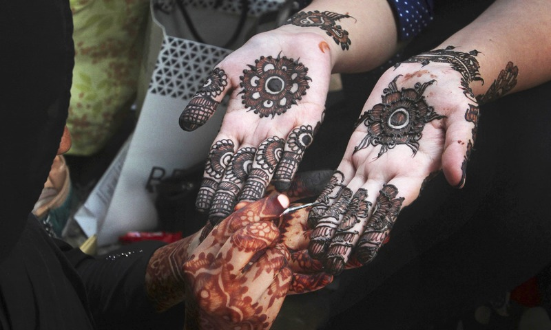 A beautician decorates a customer with traditional henna. —AP
