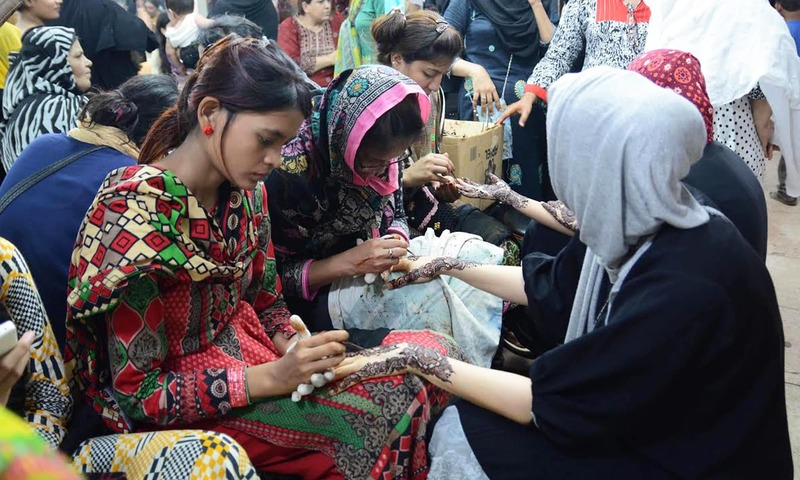 Girls are seen applying traditional henna designs on fellow girls at a market in Karachi. —APP