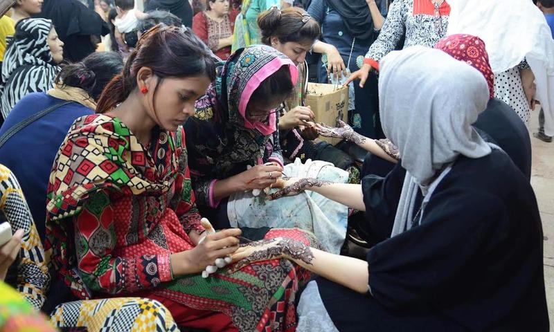کراچی میں لڑکیاں مہندی کے ڈیزائن بنوا رہی ہیں۔ — اے پی پی/فائل