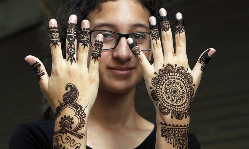 A girl displays her hands that are decorated with traditional henna in preparation for the Eid. —AP
