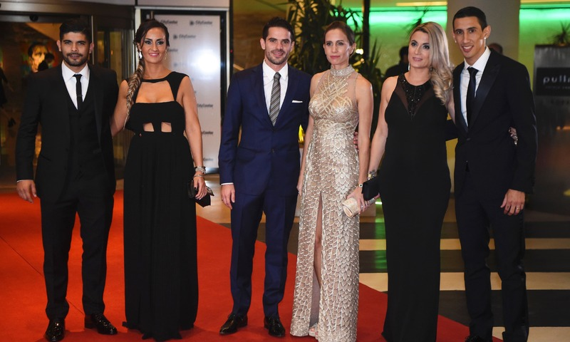 Paris Saint Germain's footballer Angel di Maria (R), Boca Juniors' footballer Fernando Gago (C) and Sevilla's footballer Ever Banegas pose with their wives during Argentine football star's wedding. —AFP