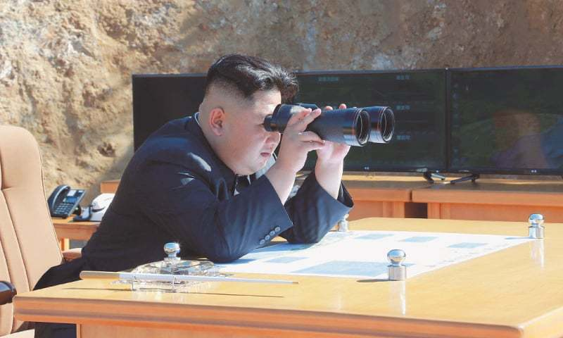 North Korean Leader Kim Jong-Un looking on (left) during the missile test on Tuesday. The order to carry out the test-fire of the intercontinental ballistic missile Hwasong-14 as signed by the North Korean leader is seen on a big screen near the Pyongyang Railway Station in Pyongyang on Tuesday.—Agencies