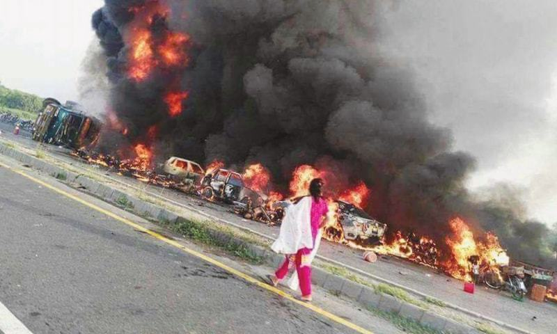 BAHAWALPUR: A woman watches vehicles in flames after a large number of people were burnt alive when an oil tanker skidded off the road and exploded.—Online/File