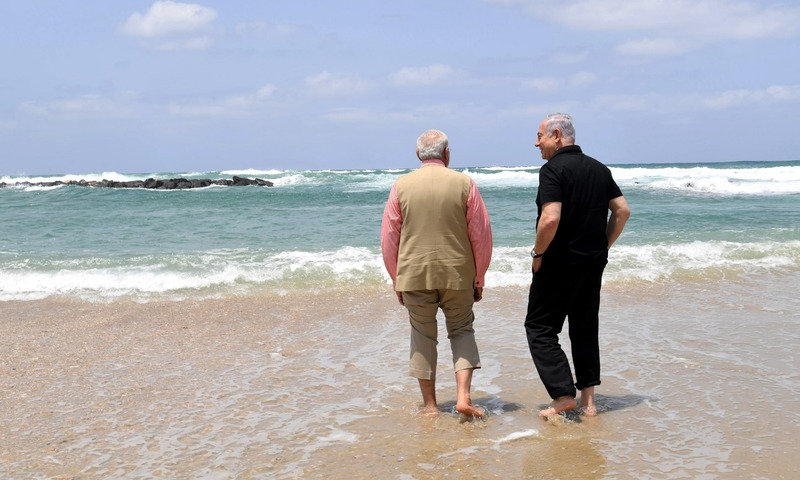 Benjamin Netanyahu walks with Narendra Modi, as they visit Olga Beach. —AFP