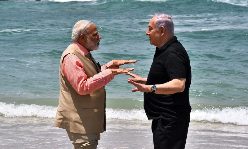 Narendra Modi and Benjamin Netanyahu gesture as they talk on Olga Beach in Hadera.. —AFP