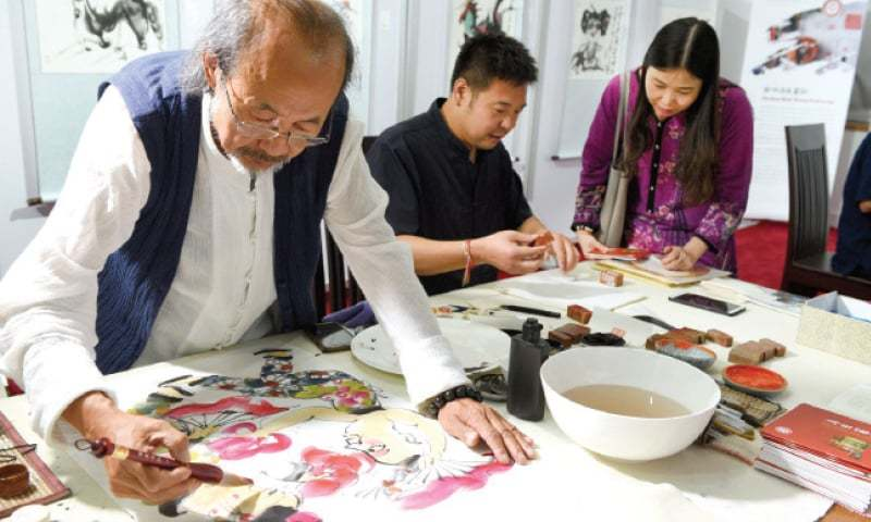 An artist busy doing the 'Chinese water colour paint' at the Chinese Cultural Heritage Week that started in Islamabad on Friday. The other picture shows works known as 'Liaonan Dough Modeling'. — White Star