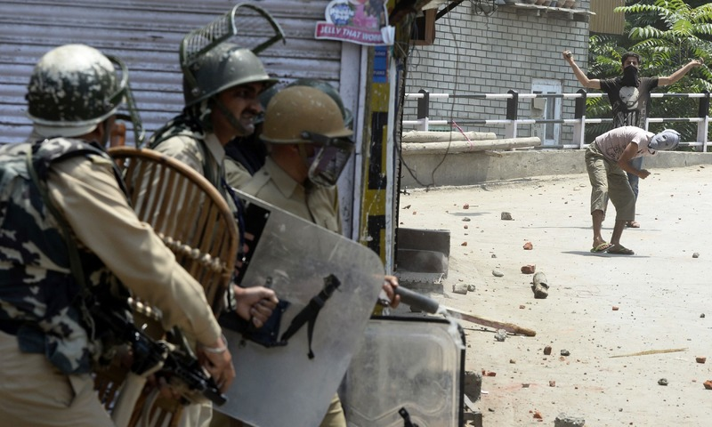 Kashmiri protesters throw stones towards Indian government forces during clashes in Srinagar. —AFP
