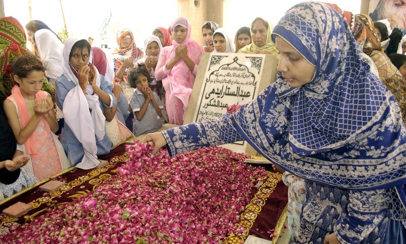 A woman showering rose on the grave of great philanthropist Abdul Sattar Edhi on the occasion of his first death anniversary. —Online