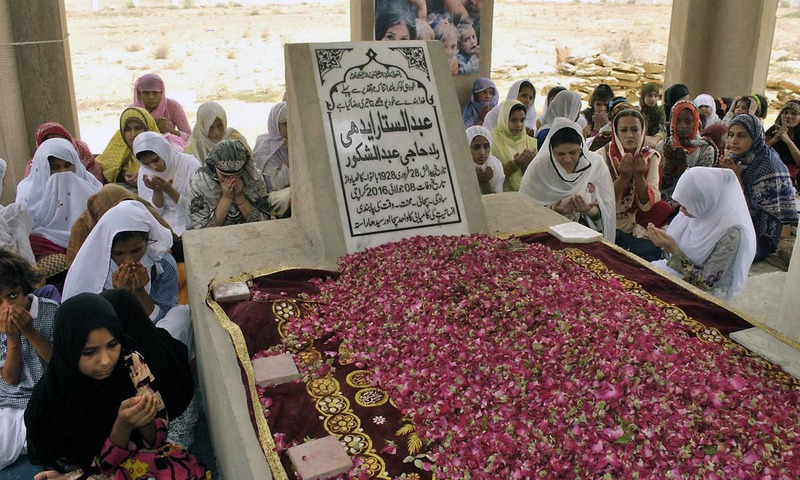Edhi Center staff and children offering fateha on the grave of Abdul Sattar Edhi. —Online