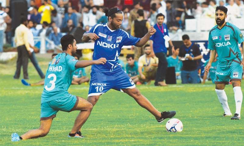 LAHORE: Brazilian football legend Ronaldinho (C) evades a challenge by Pakistan international Mohammad Ahmed during an exhibition match at the Fortress Stadium on Sunday.—M.Arif/White Star