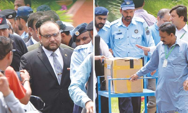 Police and court officials transport a box of final evidence presented by the JIT at the Supreme Court. — AFP