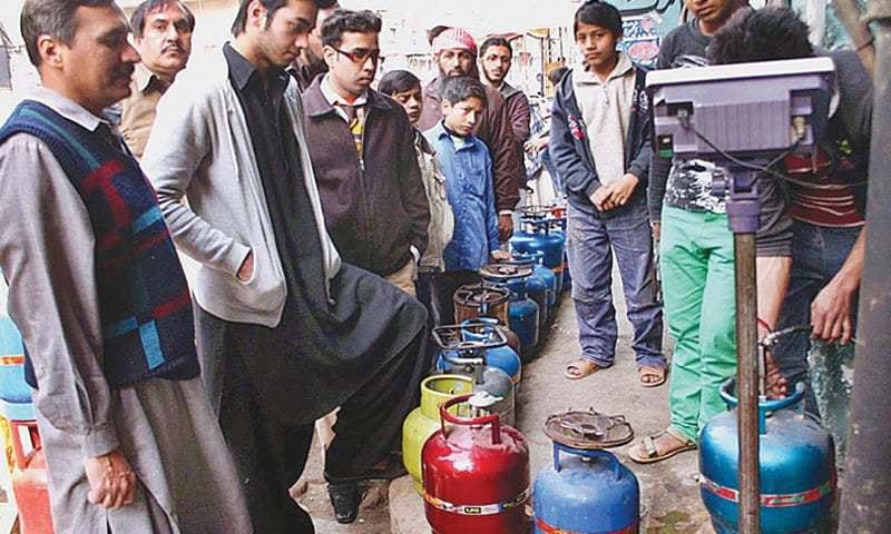 RAWALPINDI: LPG consumers wait for their turn at a refilling station. Earlier this year, the government had notified a relaxation of the moratorium on new gas connections for industrial, commercial and captive consumers.—File photo