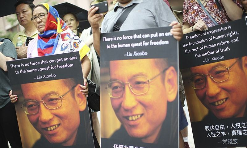 Participants, one wearing a Tibetan flag, hold photos of Liu Xiaobo during a vigil honouring Xiaobo's legacy and to protest continued human rights abuses in China, July 13, in New York.— AP