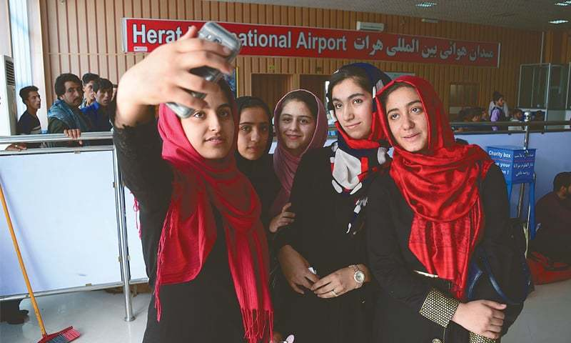 This July 13 photo shows girls from the Afghanistan Robotic House taking a selfie at Herat International Airport before embarking for the United States.—AFP