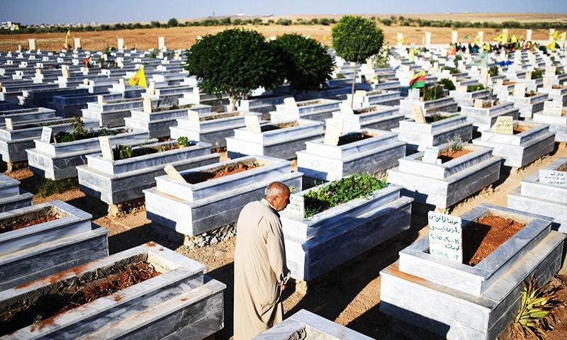 A Syrian man mourns near graves of fighters in a graveyard in the Kurdish town of Kobane in northern Syria.—AFP