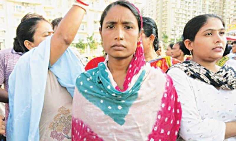 Haseena Bibi stands in front of a crowd of shouting maids opposite the Mahagun Moderne residential complex in New Delhi.─The Washington Post