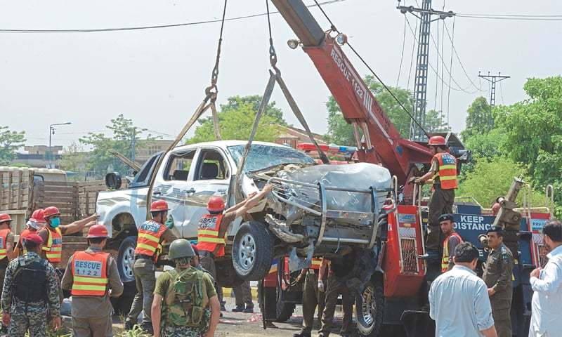Peshawar Officials use a crane to lift a security vehicle at the site of a suicide bomb attack on Monday. A military officer was martyred and 10 other people were injured when a suicide bomber struck the vehicle carrying personnel of the Frontier Corps