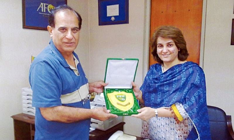 In this July 27, 2011 photo provided by the PFF, PFF secretary general Col Ahmed Yar Khan Lodhi presents a shield to departing finance manager Nadia Naqvi at its headquarters in Lahore.