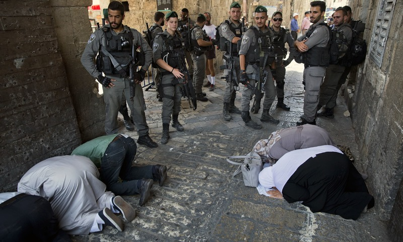 Palestinians pray as Israeli border police officers stand guard at the Lion's Gate in Jerusalem's Old City. —AP