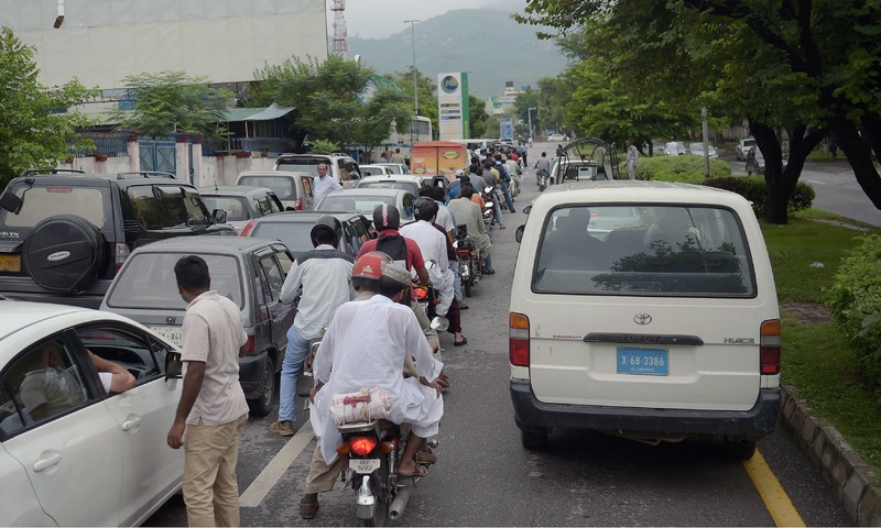 Commuters queue for fuel at a PSO station amid a countrywide strike. —AFP