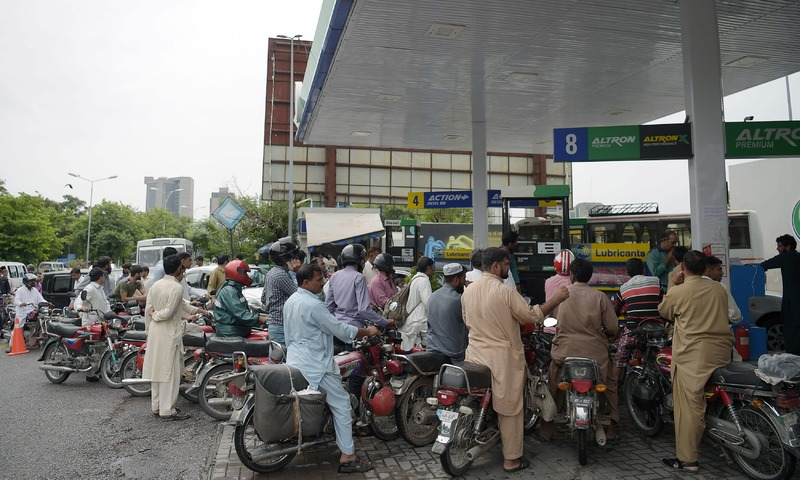 Commuters queue for fuel at a PSO station in Islamabad. —AFP