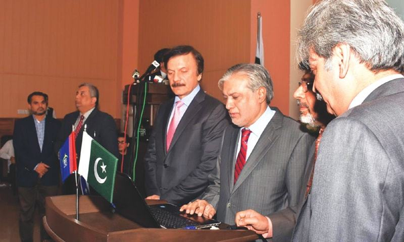 FINANCE Minister Ishaq Dar presses a keyboard button to launch the Parliamentarians Tax Directory-2016 at the FBR House on Thursday.—Online
