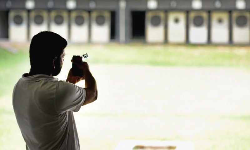 A Club Trainer Aims At Target In Indoor Shooting Range